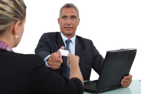 55 60 years: Woman handing over her business card during a meeting Stock Photo