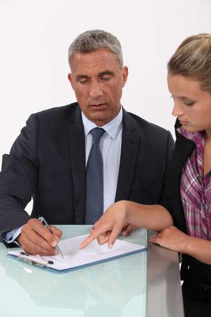 55 60 years: Secretary helping her boss fill in paperwork