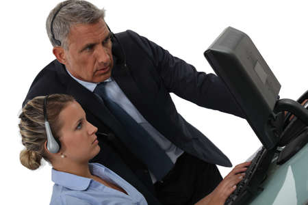 Business people with headsets looking at a computer screen photo