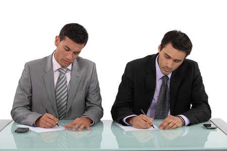 filling in: Businessmen filling in forms