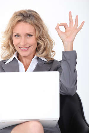 confirm confirmation: Blonde businesswoman with a laptop giving the OK sign Stock Photo