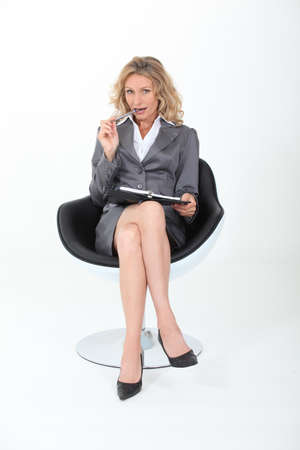 enticing: businesswoman sitting cross-legged with a flirtatious look
