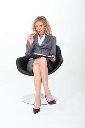 businesswoman sitting cross-legged with a flirtatious look