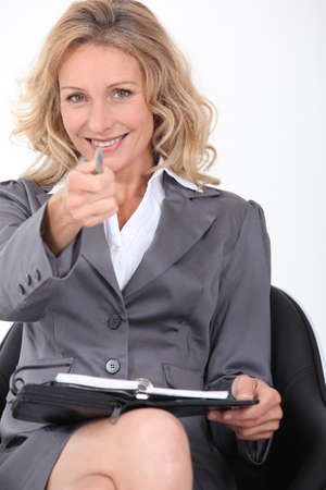 Smiling businesswoman pointing her pen  at the camera photo