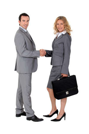 Smart suited man and woman shaking hands photo