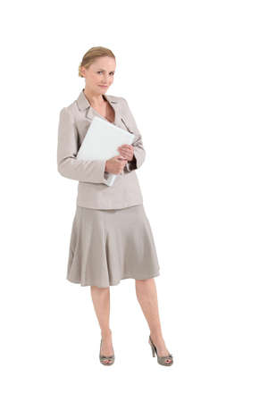 skirt suit: Woman in a beige skirt suit with a folder