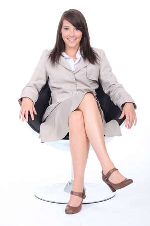 secretary skirt: Young woman in a beige skirt suit sitting in a swivel chair
