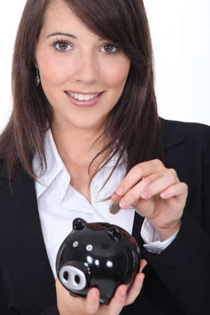 Young woman smiling putting coin in a piggy bank photo