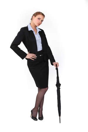 austere: Austere businesswoman holding an umbrella