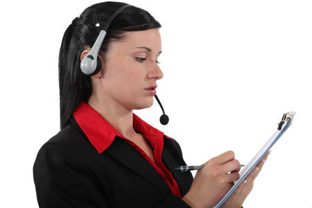 Brunette call center worker with clip-board and pen photo