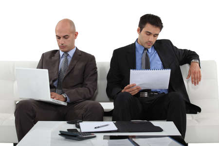 shirtsleeves: Two determined businessmen sat waiting for presentation