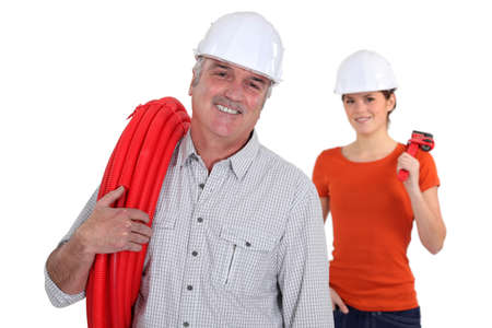 generation gap: Experienced tradesman with his assistant in the background