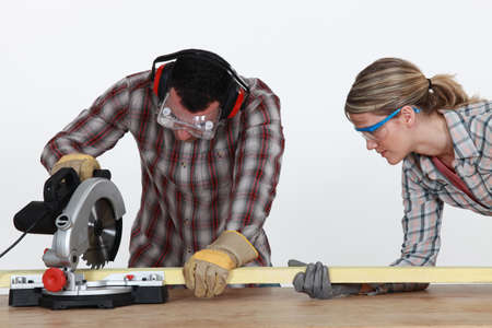 Couple sawing timber photo
