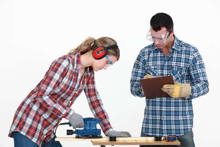 eye protection: Man evaluating a tradeswoman on her use of a jigsaw