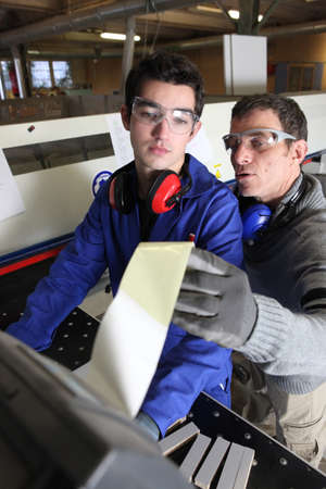 apprentice: Two factory workers stood by machine Stock Photo