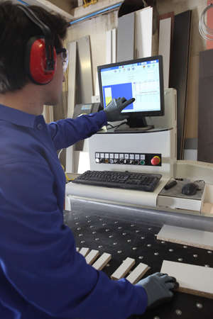 Man stood by computer operated factory machine photo