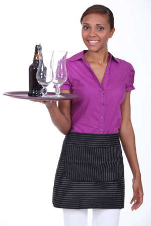 stewardess: Pretty waitress carrying a bottle of beer and two glasses on a tray