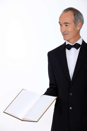 dapper: Grey haired restaurant worker presenting menu Stock Photo