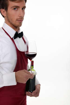 alcohol server: Sommelier serving a bottle of wine