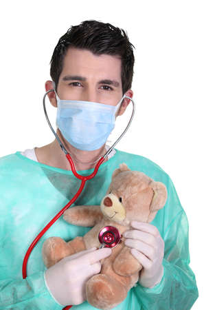 Doctor con un estetoscopio y oso de peluche photo
