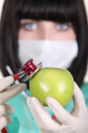 Medic using a stethoscope on an apple Stock Photo - 15118979