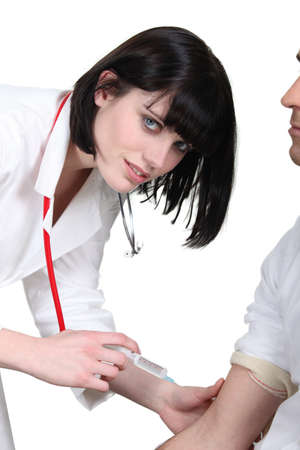Doctor injecting a male patient photo