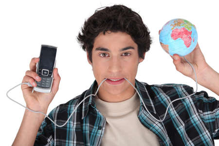 Young man with his cellphone plugged into the world Stock Photo - 15119554