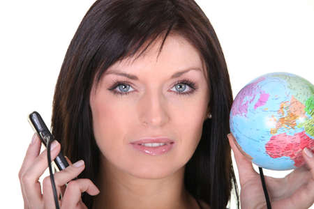 woman holding globe and cell phone with charger photo
