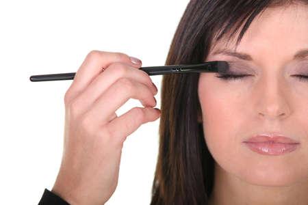 putting on: beautiful woman putting some eye shadow