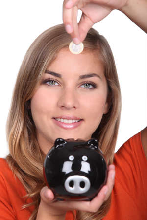 secrete: Woman holding piggy bank and coin Stock Photo