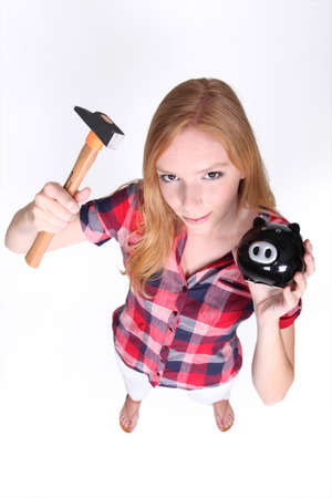 vested: Teenager with hammer and piggy-bank Stock Photo