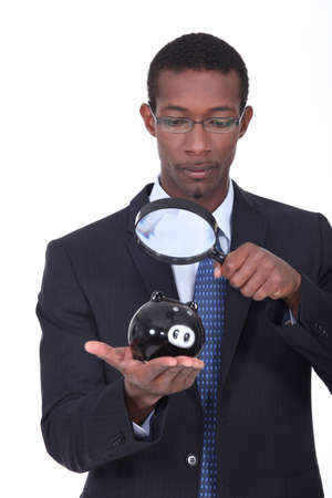 Man observing a piggy bank photo