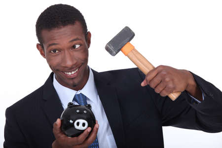 american banker: Man trying to break into a piggy bank with a hammer