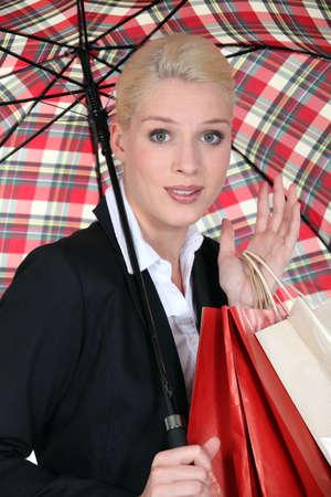 brolly: Female shopper under a brolly Stock Photo