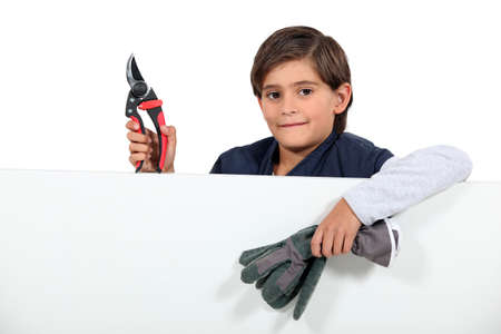 grabbing at the back: Child with pruning shears Stock Photo