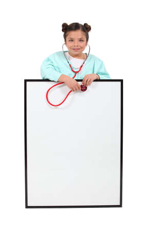 A little girl playing at being a doctor  Stock Photo - 15154332
