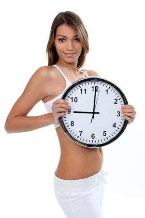 wit ondergoed: Vrouw in wit ondergoed met een klok met 9 o Stockfoto