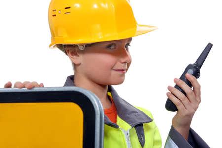 fancy dress costume: little child dressed in road man is holding a talkie walkie