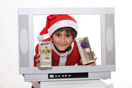 Little boy in Christmas dress behind TV screen photo