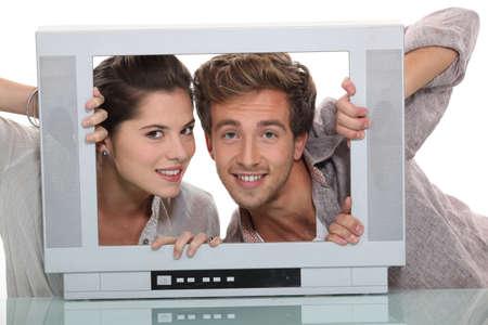 pareja viendo tv: Pareja en una pantalla de televisi�n vac�a