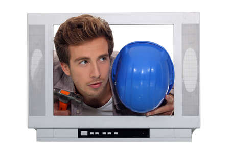 inattentive: Young man and his hard hat stuck in a television screen