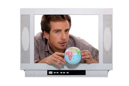 a 25 years old man behind a television screen is taking a little globe Stock Photo - 15154475