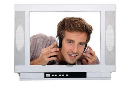 speakers desk: man with headphones behind TV