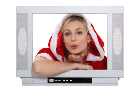Woman dressed in festive outfit blowing kiss through television photo