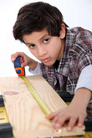 poker faced: Young boy measuring a plank of wood