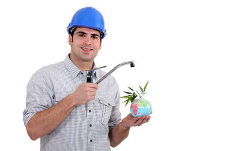 tradesperson: Plumber holding a faucet over a mini globe