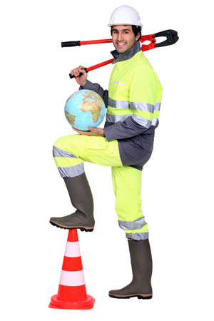 high visibility: Tradesman holding a globe and a pipe wrench Stock Photo