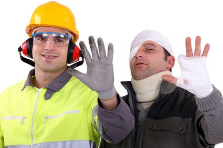 seguridad e higiene: Herido comerciante comparando su mano a un colega saludable Foto de archivo