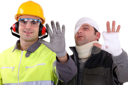safety hat: Injured tradesman comparing his hand to a healthy colleague