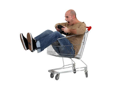 purchasing: Man pretending to drive trolley Stock Photo